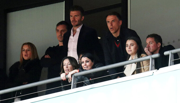 Salford City co-owners Gary Neville, second left, David Beckham, center, and Phil Neville watch the National League Play-off Soccer Final at Wembley Stadium, London, Saturday, May 11, 2019. David Beckham watched on at Wembley as Salford secured their Football League place with a 3-0 win over AFC Fylde in the Vanarama National League play-off final. The former England captain joined some of his fellow co-owners from Manchester United's 'Class of 92' to cheer on Graham Alexander's side as the club secured promotion to the Football League for the first time. (Bradley Collyer/PA via AP)
