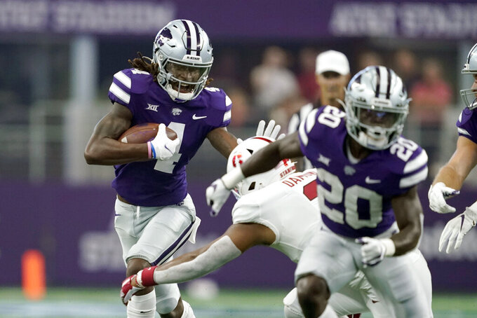 Kansas State wide receiver Malik Knowles (4) attempts to fight of a tackle attempt by Stanford linebacker Levani Damuni, right rear, in the first half of an NCAA college football game in Arlington, Texas, Saturday, Sept. 4, 2021. (AP Photo/Tony Gutierrez)