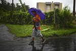 A man walks in the rain in Yabucoa, before the arrival of Tropical Storm Karen, in Yabucoa, Puerto Rico, Tuesday, Sept. 24, 2019. Karen regained tropical storm strength as it swirled toward Puerto Rico, where it's expected to bring heavy rains and strong winds. (AP Photo/Carlos Giusti)