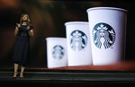 Michelle Burns, Starbucks senior vice president for coffee and tea, stands next to an image of Starbucks cups as she speaks Wednesday, March 20, 2019, during the company's annual shareholders meeting in Seattle. (AP Photo/Ted S. Warren)