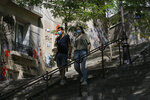 A couple walk down the stairs in the Montmartre district Monday, Aug. 10, 2020 in Paris. People are required to wear a mask outdoors starting on Monday in the most frequented areas of the French capital. The move comes as the country sees an uptick in virus infections. (AP Photo/Michel Euler)