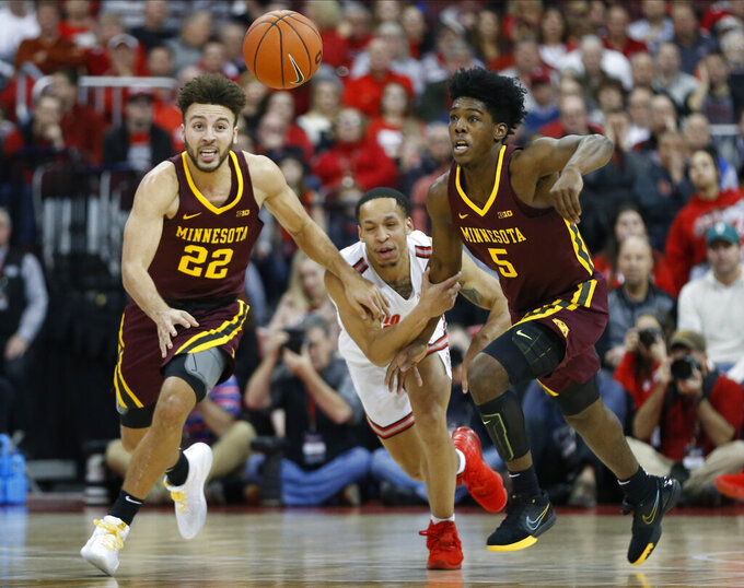 Ohio State's C.J. Walker, center, Minnesota's Gabe Kalscheur, left, and Marcus Carr chase a loose ball during the first half of an NCAA college basketball game Thursday, Jan. 23, 2020, in Columbus, Ohio. (AP Photo/Jay LaPrete)