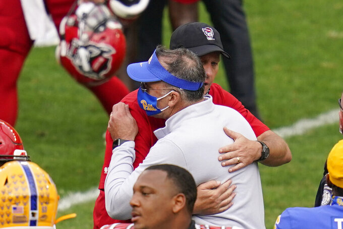 Pittsburgh head coach Pat Narduzzi, front, hugs North Carolina State head coach Dave Doeren after an NCAA college football game, Saturday, Oct. 3, 2020, in Pittsburgh. North Carolina State won 30-29. (AP Photo/Keith Srakocic)