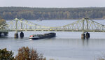 In this Wednesday, Oct. 23, 2019 photo a ship drives past the 'Glieniker Bruecke' (Glienicke Bridge) in Potsdam, Germany. During the Cold War, the Glienicke Bridge connecting West Berlin to Potsdam in East Germany was famously used as a site for exchanging captured foreign agents. Since the two opposing sides couldn't agree to work together when the bridge required repairs, each conducted them separately. The paint was applied differently and faded un-uniformly, and the two shades of green meeting at the middle of the bridge are still clearly visible today. (AP Photo/Michael Sohn)