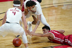 Wisconsin's Jonathan Davis, right, grabs for a loose ball, between Rutgers' Paul Mulcahy (4) and Caleb McConnell during the first half of an NCAA college basketball game against Rutgers, Friday, Jan. 15, 2021, in Piscataway, N.J. (AP Photo/Seth Wenig)
