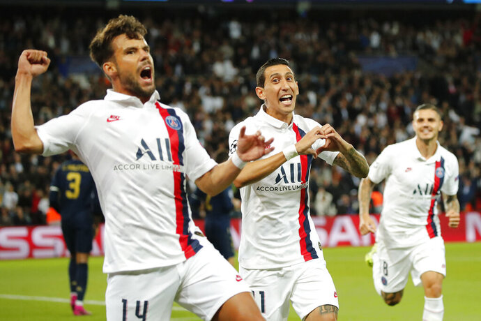 PSG's Angel Di Maria, center, celebrates with his teammates PSG's Juan Bernat, left, and PSG's Mauro Icardi after scoring his side's opening goal during the Champions League group A soccer match between PSG and Real Madrid at the Parc des Princes stadium in Paris, Wednesday, Sept. 18, 2019. (AP Photo/Francois Mori)