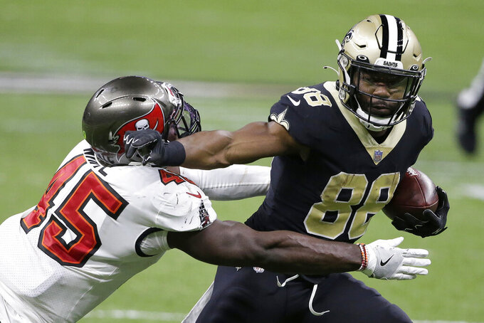 New Orleans Saints running back Ty Montgomery (88) runs against Tampa Bay Buccaneers inside linebacker Devin White (45) during the second half of an NFL divisional round playoff football game, Sunday, Jan. 17, 2021, in New Orleans. (AP Photo/Butch Dill)
