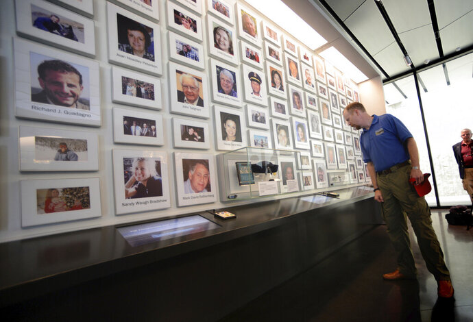 In this undated photo, Gordon Felt, right, whose brother Edward Felt perished aboard Flight 93, views a wall of photographs of the passengers and crew of the aircraft at the Flight 93 National Memorial visitors center in Shanksville, Pa. Since opening in 2011, the National Park Service and partners have worked to restore the land to its natural beauty.  (Sean Hamill/Pittsburgh Post-Gazette via AP)