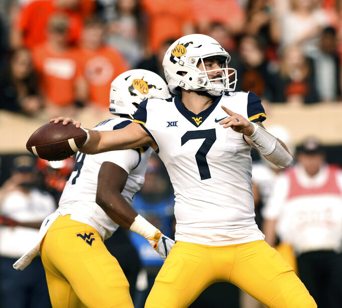 File-This Nov. 17, 2018, file photo shows West Virginia quarterback Will Grier throwing a pass during the first half of an NCAA college football game in Stillwater, Okla. NFL scouts, coaches and prospects have gathered in Mobile, Alabama, for the Senior Bowl. The game for top senior NFL prospects and junior graduates will feature quarterbacks like Missouri's Drew Lock, Grier and Duke's Daniel Jones. (AP Photo/Brody Schmidt, File)