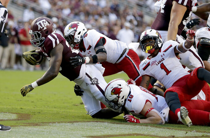 Texas A&M running back Isaiah Spiller (28) crosses the goal line for a touchdown as Lamar linebacker Dallas Martin (10) and defensive back Kyron Norwood (9) defend during the first half of an NCAA college football game, Saturday, Sept. 14, 2019, in College Station, Texas. (AP Photo/Sam Craft)
