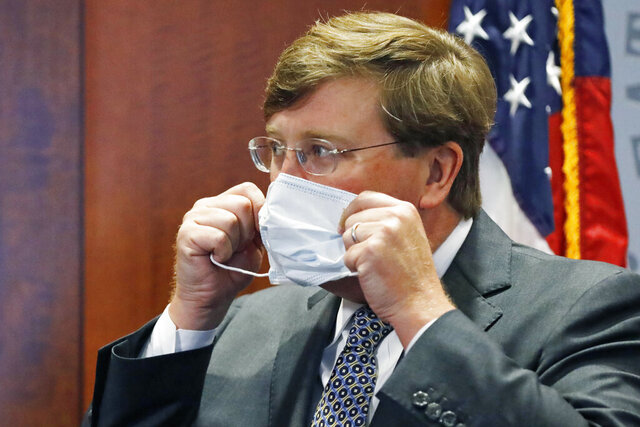 Gov. Tate Reeves adjusts his face mask as he prepares to leave his COVID-19 press briefing, Wednesday, Aug. 5, 2020, in Jackson, Miss. The governor, who has admitted to disliking the wearing of a face mask, nevertheless wears one in public, and Tuesday issued a statewide order for people to wear masks in public amid a recent surge in cases of the new coronavirus. He and other state officials provided an update on the coronavirus and the state's ongoing strategy to limit transmission. (AP Photo/Rogelio V. Solis)