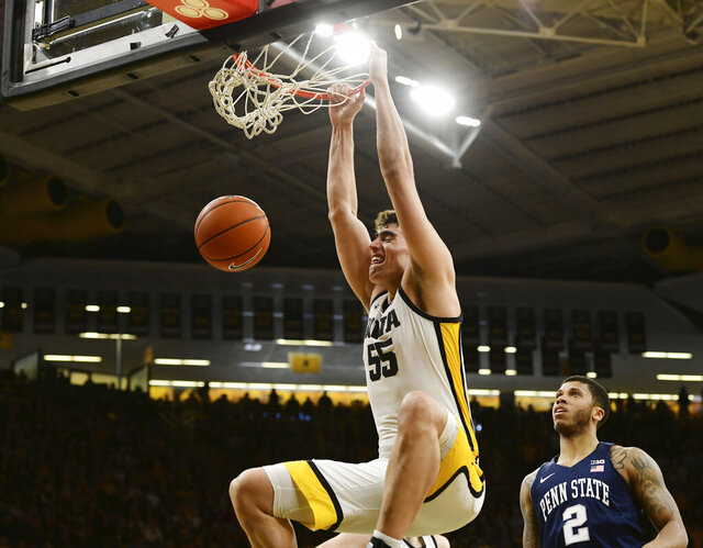 FILE - In this Feb. 29, 2020, file photo, Iowa's Luka Garza (55) dunks as Penn State's Myles Dread (2) looks on during the second half of an NCAA college basketball game in Iowa City, Iowa. Big Ten player of the year Garza says he is withdrawing from the NBA draft and will return to Iowa for his senior season. Garza says his heart is in Iowa City and that it would have been hard to close the book on his college career without a last chapter. (AP Photo/Cliff Jette, File)