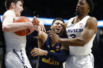 Marquette's Markus Howard, center, competes for a rebound against Xavier's Zach Freemantle, left, and Quentin Goodin during the second half of an NCAA college basketball game, Wednesday, Jan. 29, 2020, in Cincinnati. Howard was injured on the play. (AP Photo/John Minchillo)