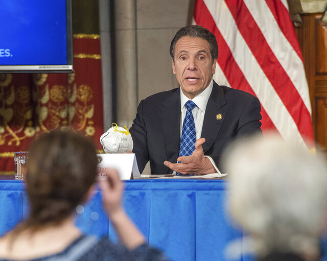 In this April 24, 2020 photo provided by the Office of Governor Andrew M. Cuomo, Gov. Cuomo addresses the media while holding an n95 mask during his daily press briefing on COVID-19, Coronavirus, at the State Capitol in Albany, N.Y. The mask was sent to the governor by a retired farmer from Kansas whose wife only has one lung. (Darren McGee/Office of Governor Andrew M. Cuomo via AP)