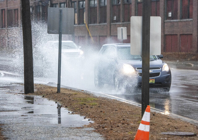 Cars splash through puddles on Friday, Dec. 25 2020 in Auburn, Maine.    A storm packing a mix of heavy winds and rain knocked out power to thousands of homes across the Northeast region Christmas morning. (Andree Kehn/Sun Journal via AP)