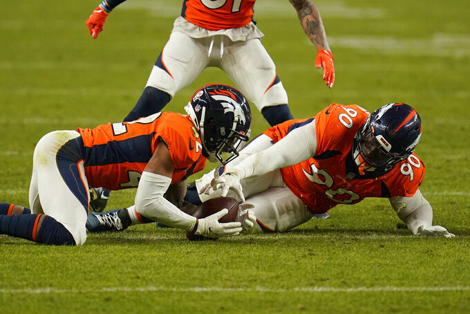 Denver Broncos cornerback Parnell Motley (42) recovers a fumble by the Las Vegas Raiders beside nose tackle DeShawn Williams (90) during the second half of an NFL football game, Sunday, Jan. 3, 2021, in Denver. (AP Photo/Jack Dempsey)