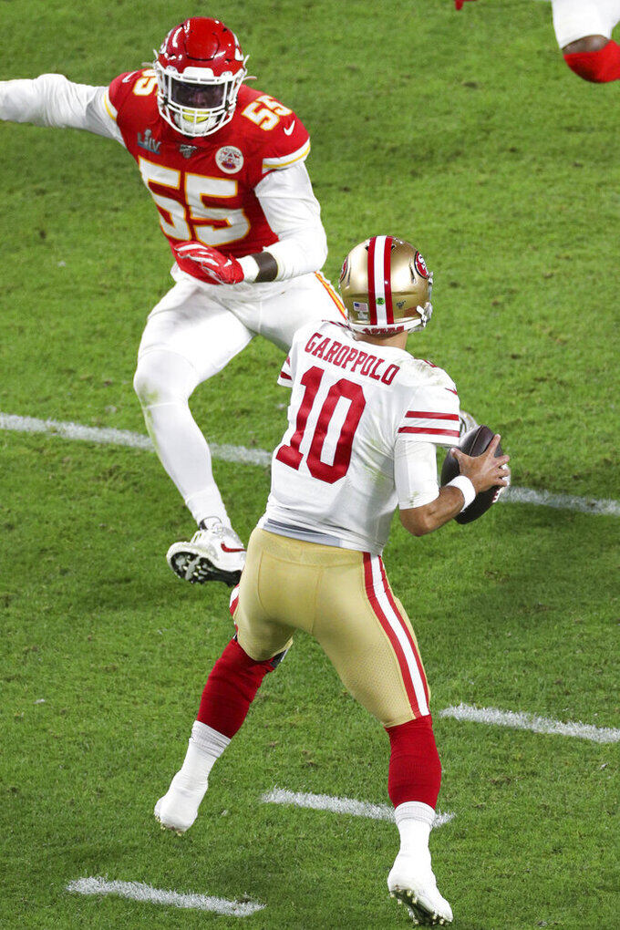 San Francisco 49ers quarterback Jimmy Garoppolo (10) looks downfield for a receiver as Kansas City Chiefs defensive end Frank Clark (55) defends in the NFL Super Bowl football game, Sunday, Feb. 2, 2020 in Miami Gardens, Fla. The Chiefs defeated the 49ers 31-20.(Margaret Bowles via AP)