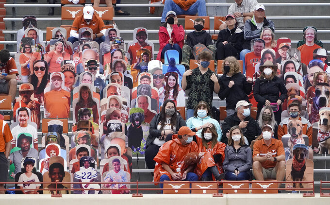 Fans wear face masks during an NCAA college football game between Texas and Iowa State, Friday, Nov. 27, 2020, in Austin, Texas. (AP Photo/Eric Gay)