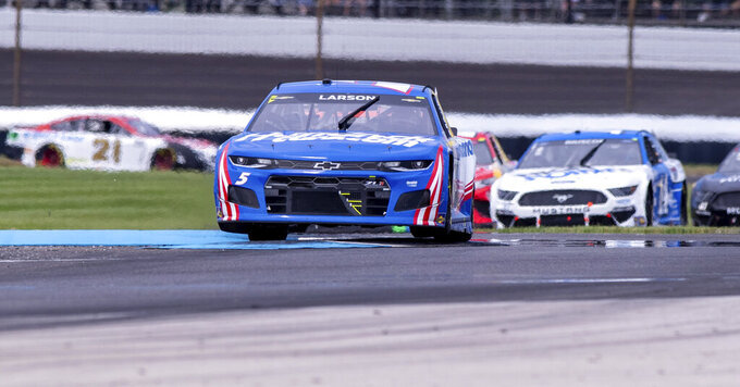 The car driven by Kyle Larson (5) flies off a curb at Turn 5 during a NASCAR Cup Series auto race at Indianapolis Motor Speedway, Sunday, Aug. 15, 2021, in Indianapolis. (AP Photo/Doug McSchooler)