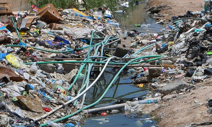 In this Saturday, July, 20, 2019 photo, potable water pipes mix with sewage at garbage dump in Basra, Iraq. A leading human rights organization has accused Iraqi authorities of failing to properly address underlying causes for an ongoing water crisis in Iraq's southern region. A report issued Monday by Human Rights Watch on the chronic water shortages and pollution in Iraq's Basra province says authorities continue to allow activities that pollute Basra's water resources despite the health risks to residents. (AP Photo/Nabil al-Jurani)