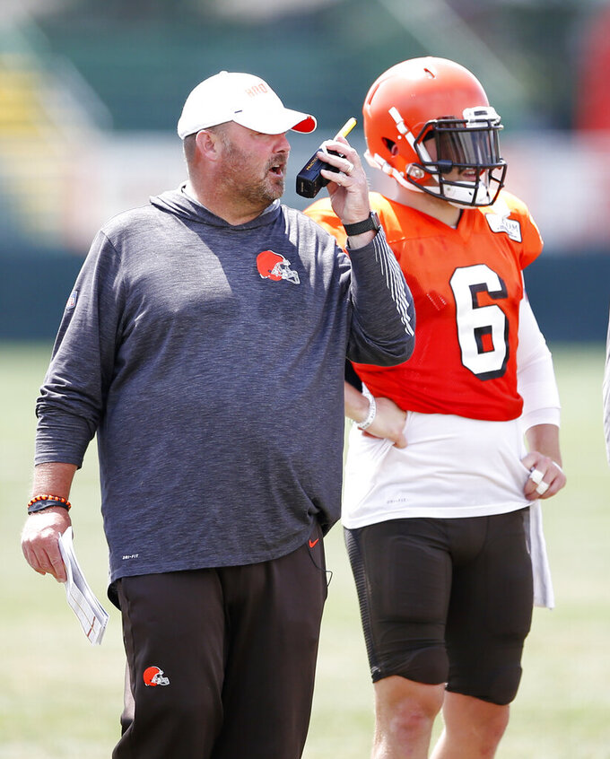 Cleveland Browns head coach Freddie Kitchens calls in a play as quarterback Baker Mayfield (6) looks on during practice at the NFL football team's training facility Monday, Aug. 5, 2019, in Berea, Ohio. (AP Photo/Ron Schwane)