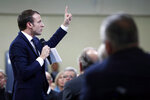 French President Emmanuel Macron gestures as he speaks during a meeting with mayors and local association members as part of the