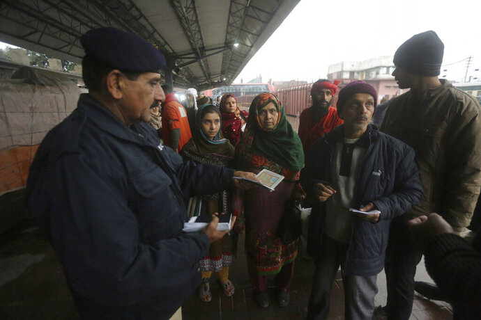 A Pakistani police officer checks documents of passengers travel to India via Samjhota Express at Lahore railway station in Pakistan, Thursday, Feb. 21, 2019.  Indian authorities suspended a bus service this week without explanation. The development comes amid escalated tensions between Pakistan and India in the wake of last week's deadly suicide bombing in Kashmir against Indian paramilitary troops. (AP Photo/K.M. Chaudary)