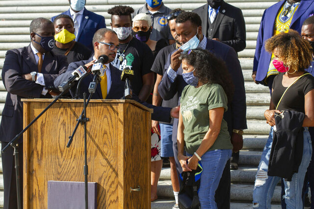 Attorney Ron Haley adjusts the microphone at the podium for Mona Hardin, center, mother of Ronald Greene, as she approaches to speak at a news conference outside the Louisiana State Capitol in Baton Rouge, La., Wednesday, Oct. 7, 2020. Attorney Lee Merritt stands directly behind Hardin. Greene died following a police chase in Louisiana in 2019, and his death is now under federal investigation. Greene's family filed a federal wrongful-death lawsuit in May alleging troopers