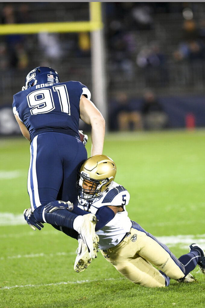 Navy cornerback Michael McMorris (5) takes down Connecticut tight end Jay Rose (91) during the first half of an NCAA college football game Friday, Nov. 1, 2019, in East Hartford, Conn. (AP Photo/Stephen Dunn)