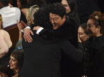 Bong Joon Ho, left, is congratulated by Kang-Ho Song before going on stage to accept the award for best international feature film for