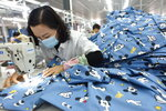 A woman wearing a mask labors in a garment factory in Donghai county in east China's Jiangsu province Tuesday, Oct. 27, 2020. China's manufacturing activity expanded in October for the eighth straight month, though at a slightly slower rate than in September, the National Bureau of Statistics said Saturday, Oct. 31, 2020. (Chinatopix Via AP)