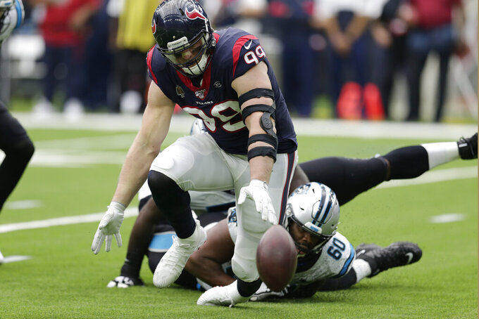 Houston Texans defensive end J.J. Watt (99) and Carolina Panthers offensive tackle Daryl Williams (60) chase a fumble during the second half of an NFL football game Sunday, Sept. 29, 2019, in Houston. Watt recovered the ball. (AP Photo/Michael Wyke)