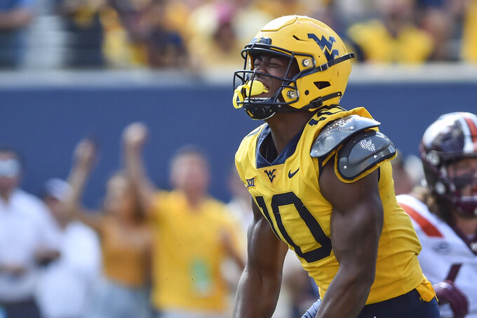 West Virginia linebacker Jared Bartlett (10) reacts after sacking Virginia Tech quarterback Braxton Burmeister (3) during the second half of  an NCAA college football game in Morgantown, W.Va., Saturday, Sep. 18, 2021. (AP Photo/William Wotring)