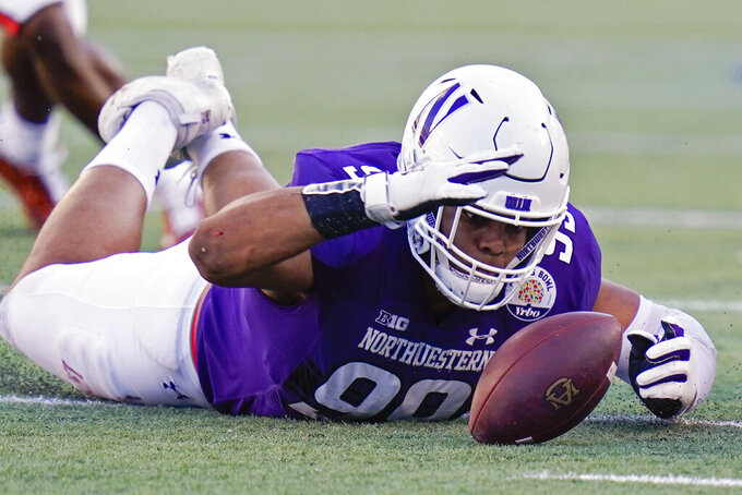 Northwestern defensive end Earnest Brown IV recovers an Auburn fumble during the second half of the Citrus Bowl NCAA college football game, Friday, Jan. 1, 2021, in Orlando, Fla. Northwestern beat Auburn 35-19. (AP Photo/John Raoux)