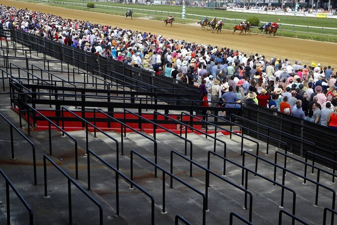 "FILE - In this May 18, 2019, file photo, horses in the day's eleventh horse race pass part of a closed grandstand at Pimlico Race Course ahead of the Preakness Stakes horse race in Baltimore. A measure in Maryland to redevelop Pimlico Race Course to keep the second leg of horse racing's Triple Crown in Baltimore is scheduled for a hearing before state lawmakers.  The ""Racing and Community Development Act of 2020"" is set for a hearing before the House Ways and Means Committee on Tuesday, Feb. 25, 2020. (AP Photo/Patrick Semansky, File)"