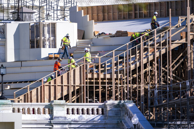 With Inauguration Day two months away on Jan. 20, 2021, construction crews work on the platforms where the president-elect will take the oath of office, at the Capitol in Washington, Nov. 18, 2020. (AP Photo/J. Scott Applewhite)