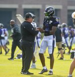 Baltimore Ravens quarterback Lamar Jackson, right, is greeted by offensive coordinator Greg Roman at the start of football practice during training camp at Under Armour Performance Center on Sunday, Aug. 7, 2021 in Owings Mills, Md. (Kevin Richardson/The Baltimore Sun via AP)