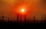 FILE - In this Oct. 11, 2019, file photo, smoke from a wildfire called the Saddle Ridge Fire hangs above power lines as the sun rises in Newhall, Calif. Pacific Gas & Electric started cutting power Sunday, Oct. 25, 2020, to tens of thousands of customers in Northern California and planned outages for many more to prevent the chance of sparking wildfires due to extreme fire weather. The nation's largest utility said outages began in the north of the state in Shasta, Tehama, Glenn, Colusa and Lake counties and were expected to continue southward throughout Sunday and possibly into Monday. (AP Photo/Noah Berger, File)