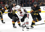 Chicago Blackhawks right wing Patrick Kane (88) vies for the puck with Vegas Golden Knights' William Karlsson (71) and Jonathan Marchessault (81) during the third period of an NHL hockey game Thursday, Dec. 6, 2018, in Las Vegas. (AP Photo/John Locher)
