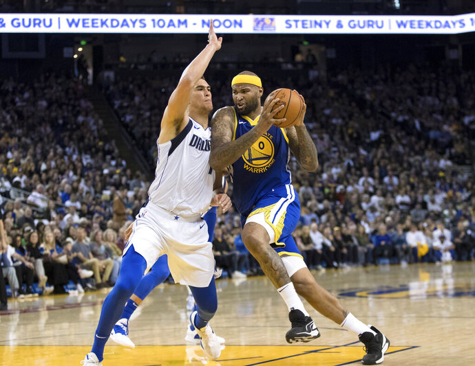 Golden State Warriors center DeMarcus Cousins, right, collides with Dallas Mavericks forward Dwight Powell in the second half of an NBA basketball game Saturday, March 23, 2019 in Oakland, Calif. (AP Photo/John Hefti)