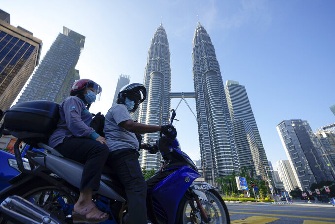 Motorists wearing face masks wait in front of the Twin Towers during the first day of Full Movement Control Order (MCO) in Kuala Lumpur, Malaysia, Tuesday, June 1, 2021. Malls and most businesses in Malaysia shuttered Tuesday asthe countrybegan its second near total coronavirus lockdown to tackle a worsening pandemic that has put its healthcare system on the verge of collapse. (AP Photo/Vincent Thian)