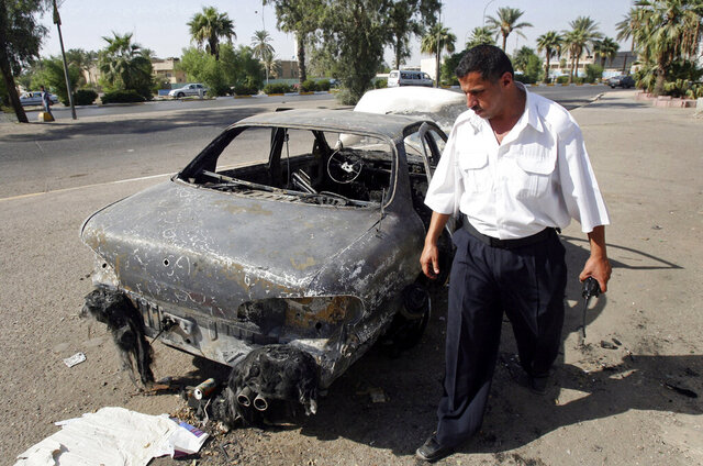 FILE - In this Sept. 25, 2007 file photo, an Iraqi traffic policeman inspects a car destroyed by a Blackwater security detail in al-Nisoor Square in Baghdad, Iraq. On Tuesday, Dec. 22, 2020, the Trump administration pardoned four military contractors convicted of killing 14 Iraqi civilians in a public square 13 years ago.  (AP Photo/Khalid Mohammed, File)