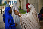 A Nigerian woman attends Friday prayers at the central mosque is security checked a day prior to the election, in Abuja, Nigeria, Friday Feb. 15, 2019.  Nigeria surged into the final day of campaigning ahead of Saturday's election, as President Muhammadu Buhari made one last pitch to stay in office while top challenger Atiku Abubakar shouted to supporters: