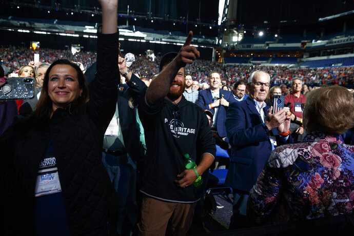 A man points at President Donald Trump after he tossed his cellphone toward the stage as Trump arrived to speak to the annual meeting of the National Rifle Association, Friday, April 26, 2019, in Indianapolis. (AP Photo/Evan Vucci)