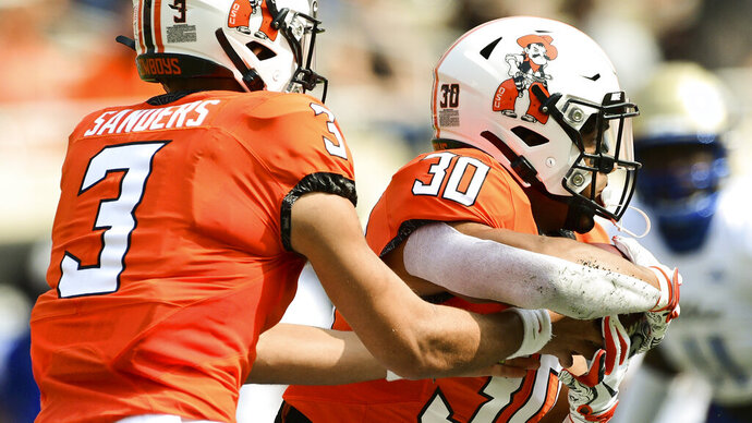 Oklahoma State quarterback Spencer Sanders (3) hands the ball off to running back Chuba Hubbard (30) duyring the first half of an NCAA college football game against Tulsa, Saturday, Sept. 19, 2020, in Stillwater, Okla. (AP Photo/Brody Schmidt)