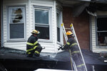Firefighters spray dow the front porch of a row home in the aftermath of a fire in Philadelphia, Tuesday, June 25, 2019. Several people, including some children, were injured trying to escape the house fire.  (AP Photo/Matt Rourke)