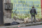 A man and his dog walk past a body bag that contains the remains of a man infected with the new coronavirus who collapsed on the street and died, according to Police Captain Diego Lopez, in Quito, Ecuador, Tuesday, May 5, 2020. The disease took longer to reach the poorer metropolitan areas, but now infections are surging in those heavily congested neighborhoods. (AP Photo/Dolores Ochoa)