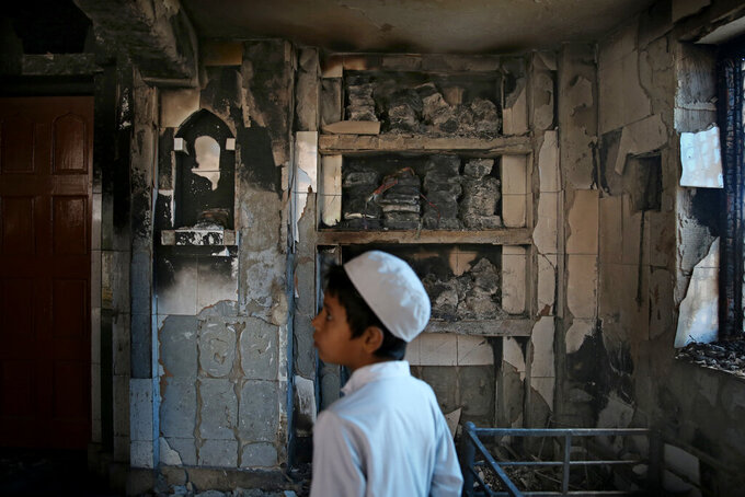 FILE - In this Thursday, Feb. 27, 2020, file photo, an Indian Muslim boy stands inside a mosque burnt in Tuesday's communal violence in New Delhi, India. As the first anniversary of bloody communal riots that convulsed the Indian capital approaches, Muslim victims are still shaken and struggling to make sense of their struggle to seek justice. Many say they have run repeatedly into a refusal by police to investigate complaints made by Muslims against Hindu rioters. (AP Photo/Altaf Qadri)