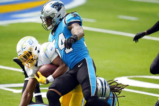 Carolina Panthers outside linebacker Shaq Thompson (54) forces a fumble from Los Angeles Chargers running back Joshua Kelley (27) during the first half of an NFL football game Sunday, Sept. 27, 2020, in Inglewood, Calif. (AP Photo/Alex Gallardo)