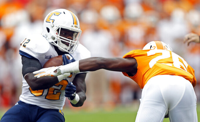 Chattanooga running back Ailym Ford (32) tries to escape from Tennessee defensive back Theo Jackson (26) in the first half of an NCAA college football game Saturday, Sept. 14, 2019, in Knoxville, Tenn. (AP Photo/Wade Payne)